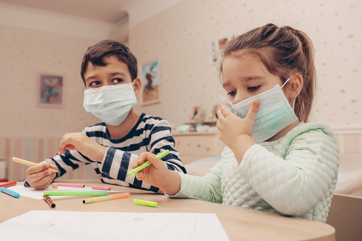 two children wearing face masks sitting at a table drawing