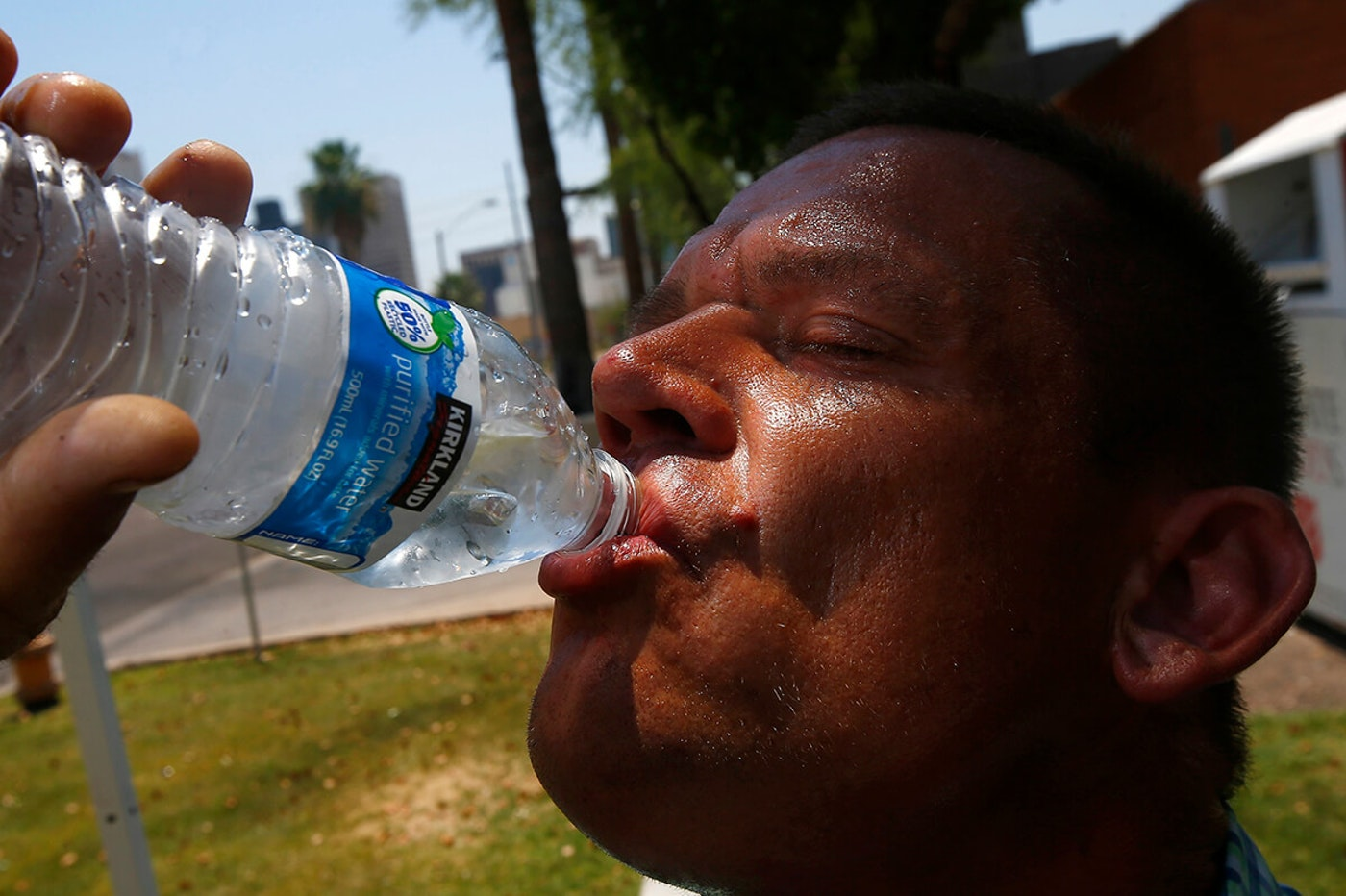 man sweating and drinking from a water bottle