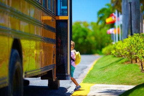 small boy boarding school bus