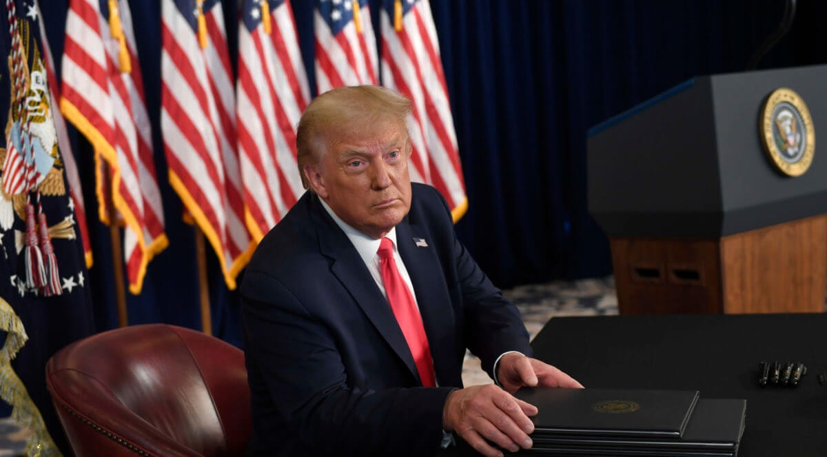 President Donald Trump prepares to sign four executive orders during a news conference at the Trump National Golf Club in Bedminster, N.J., Saturday, Aug. 8, 2020. (AP Photo/Susan Walsh)
