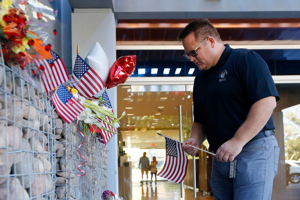 Ted Olsen, of Phoenix, looks to place an American flag at a makeshift memorial in honor of the late Arizona Republican Sen. John McCain at McCain's office Monday, Aug. 27, 2018, in Phoenix. McCain, the war hero who became the GOP's standard-bearer in the 2008 election, died at the age of 81, Saturday, Aug. 25, 2018, after battling brain cancer. (AP Photo/Ross D. Franklin)