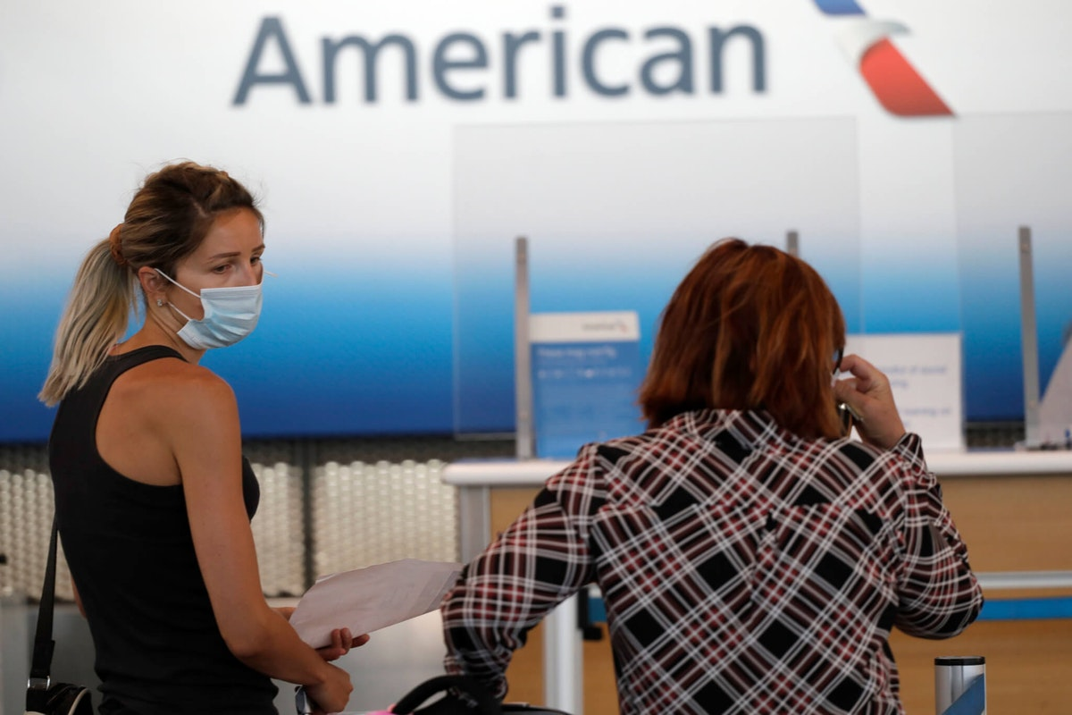FILE - In this June 16, 2020 photo, travelers wear mask as they wait at the American Airlines ticket counter in Terminal 3 at O'Hare International Airport  in Chicago.   American Airlines and Southwest Airlines reported large second-quarter losses on Thursday, July 23, 2020, as expected, and warned that the recovery in air travel that began in April has stalled as coronavirus cases surge again in the U.S. American posted a loss of more than $2 billion, and Southwest lost $915 million. (AP Photo/Nam Y. Huh)
