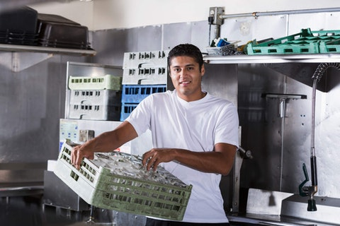 Hispanic man working as bus boy in restaurant kitchen. Photo courtesy kali9/E+/Getty Images