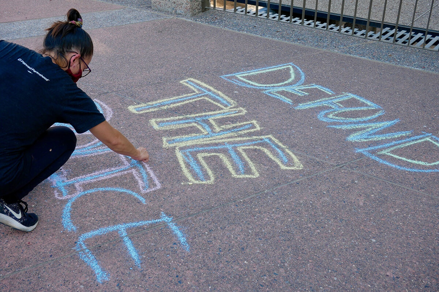 "woman writes ""defund the police"" in chalk on asphalt"