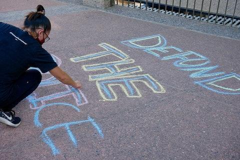 "woman writes ""defund the police"" in chalk on asphalt"