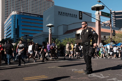 a police officer stands in downtown Phoenix as a group of protesters walks past