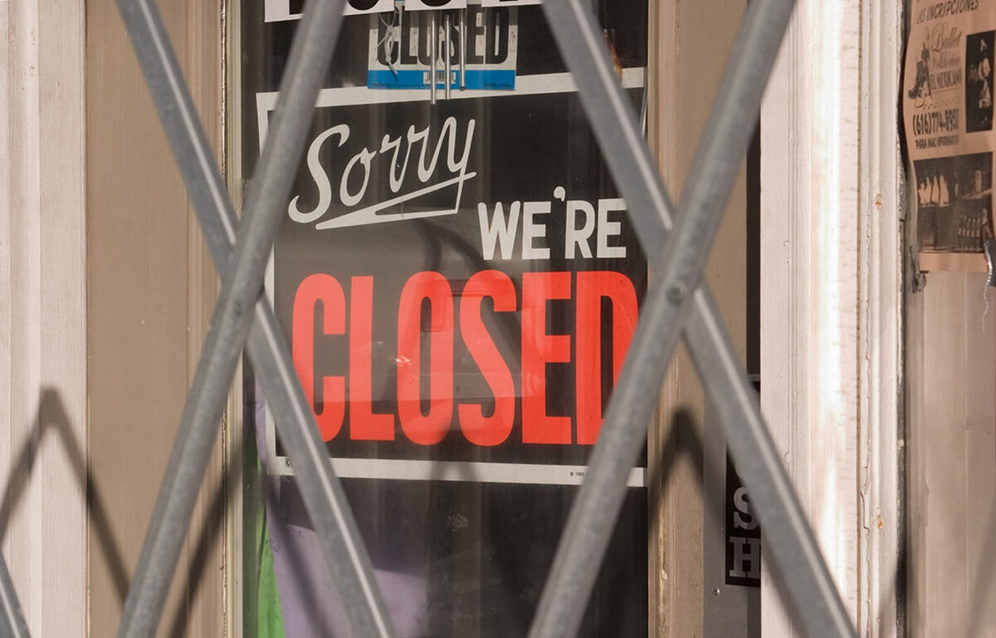 """sorry, we're closed"" sign hanging on business"