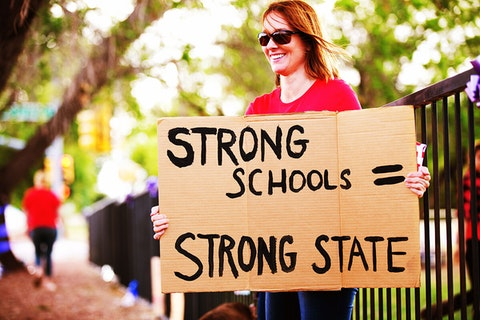 "woman holding sign that says ""strong schools equals strong state"""