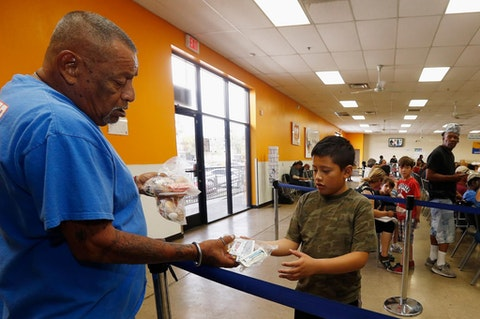 Volunteer Monroy Martinez, left, hands out a free to-go lunch to a boy at the St. Mary's Food Bank Alliance due to the Arizona teachers strike and closure of schools Thursday, April 26, 2018, in Phoenix. (AP Photo/Ross D. Franklin)