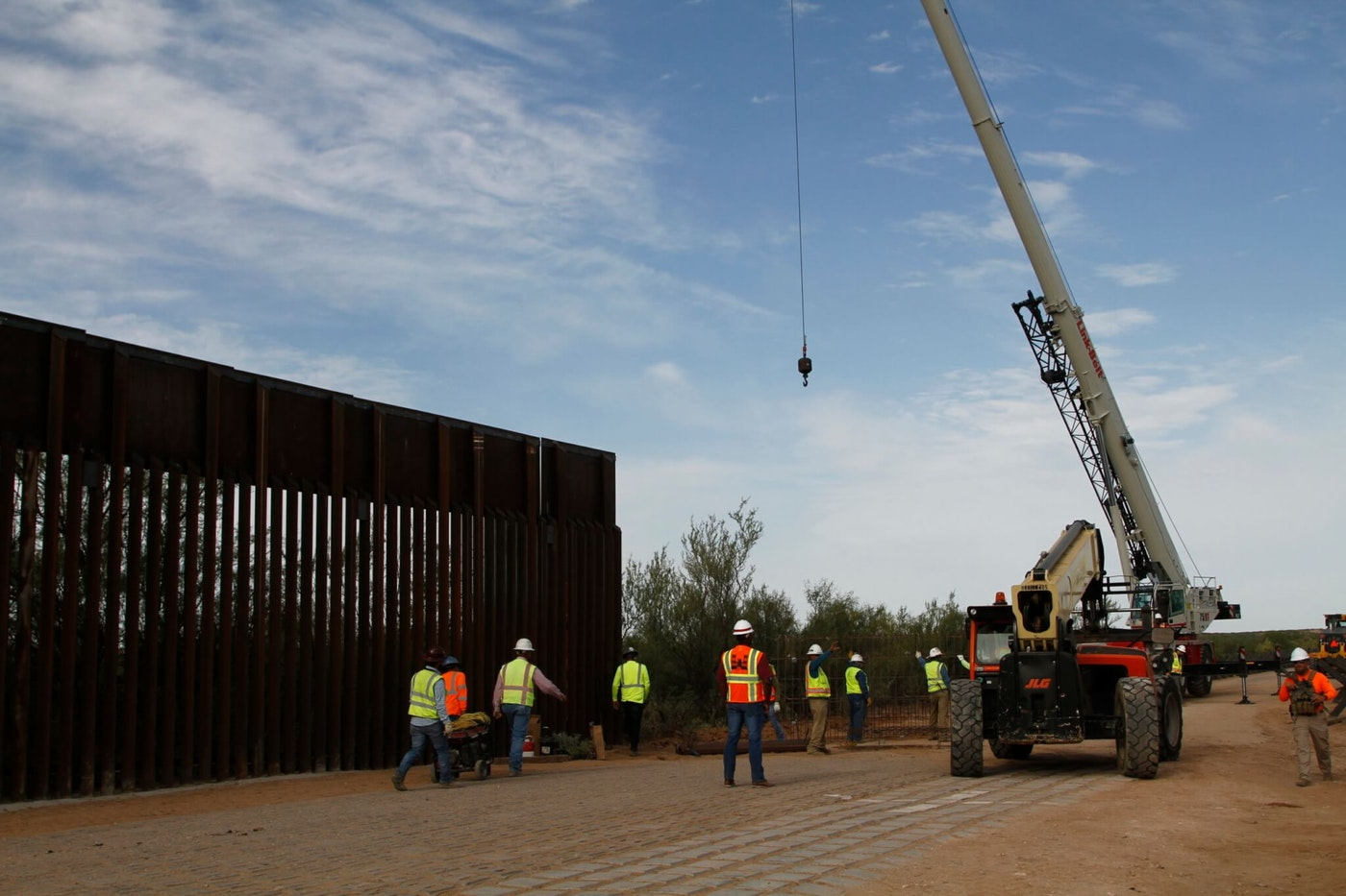 FILE - In this Aug. 23, 2019 file photo, workers break ground on new border wall construction about 20 miles west of Santa Teresa, N.M. Construction on a Pentagon-funded portion of the border wall began near Yuma, Arizona, this week, just as federal authorities announced they are diverting even more defense funds for wall projects. Crews began constructing a 30-foot steel fence along the Colorado River this week. (AP Photo/Cedar Attanasio, File)