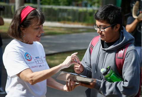 Linda Holman Bentley, left, of the League of Women Voters, helps sign up a Phoenix College student fill out a voter registration form at Phoenix College on National Voter Registration Day Tuesday, Sept. 24, 2019, in Phoenix. (AP Photo/Ross D. Franklin)