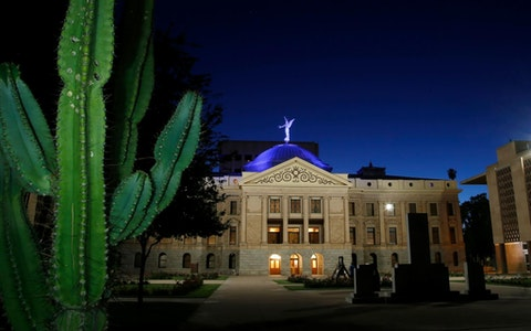 The dome of the Arizona Capitol building is illuminated in blue as buildings and structures around the state are lit in blue as a symbol of support for Arizona's frontline medical workers and emergency responders battling the coronavirus Wednesday, April 15, 2020, in Phoenix. (AP Photo/Ross D. Franklin)