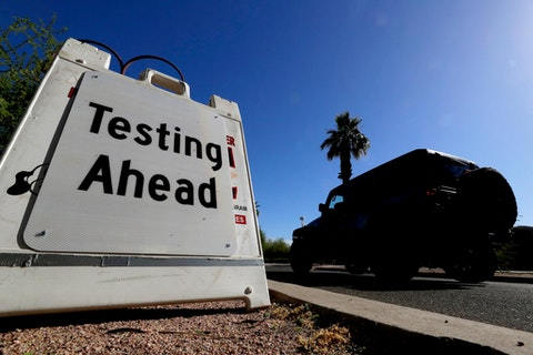 A vehicle arrives at COVID-19 testing site at Steele Indian School Park, Saturday, May 23, 2020, in Phoenix. The City of Phoenix and SonoraQuest are hosting a mobile COVID-19 testing blitz for area residents. (AP Photo/Matt York)