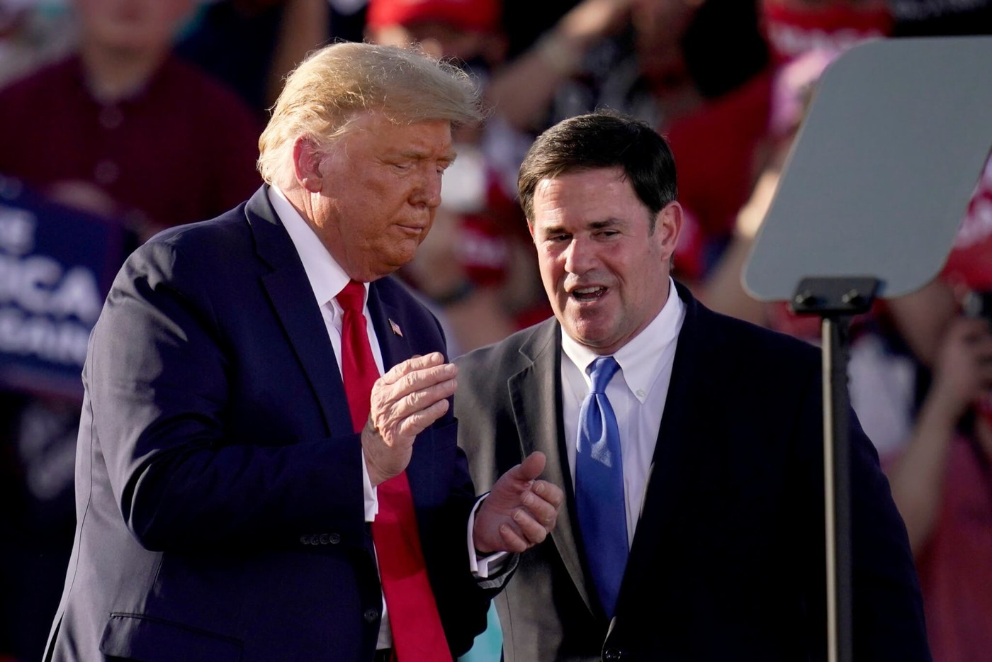 President Donald Trump, left, pauses with Arizona Gov. Doug Ducey during a campaign rally Monday, Oct. 19, 2020, in Tucson, Ariz. (AP Photo/Ross D. Franklin)
