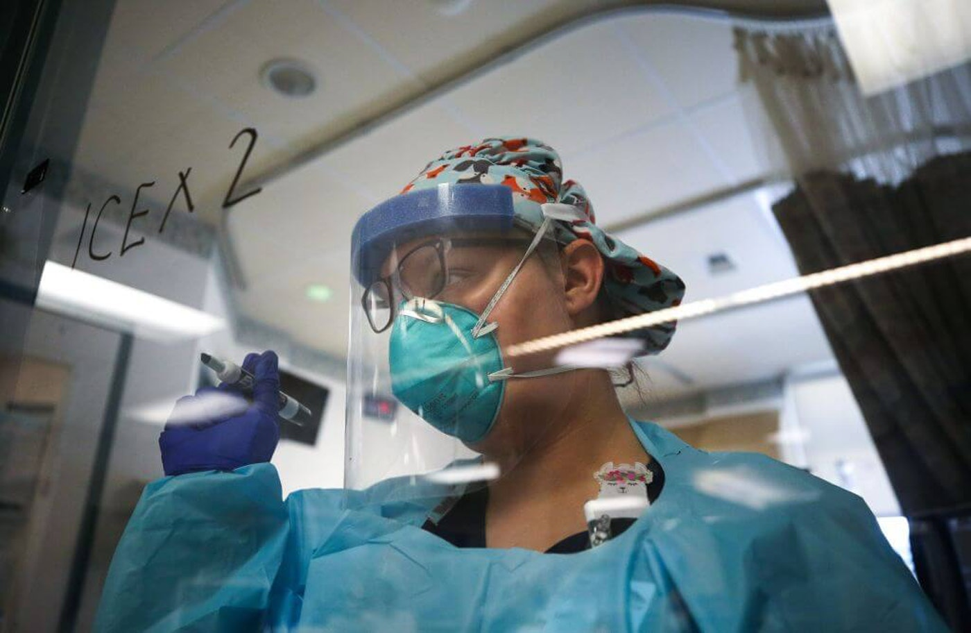 A nurse makes a note on the window of a coronavirus (COVID-19) patient's room in the Intensive Care Unit (ICU) at El Centro Regional Medical Center in hard-hit Imperial County on July 28, 2020 in El Centro, California. (Photo by Mario Tama/Getty Images)