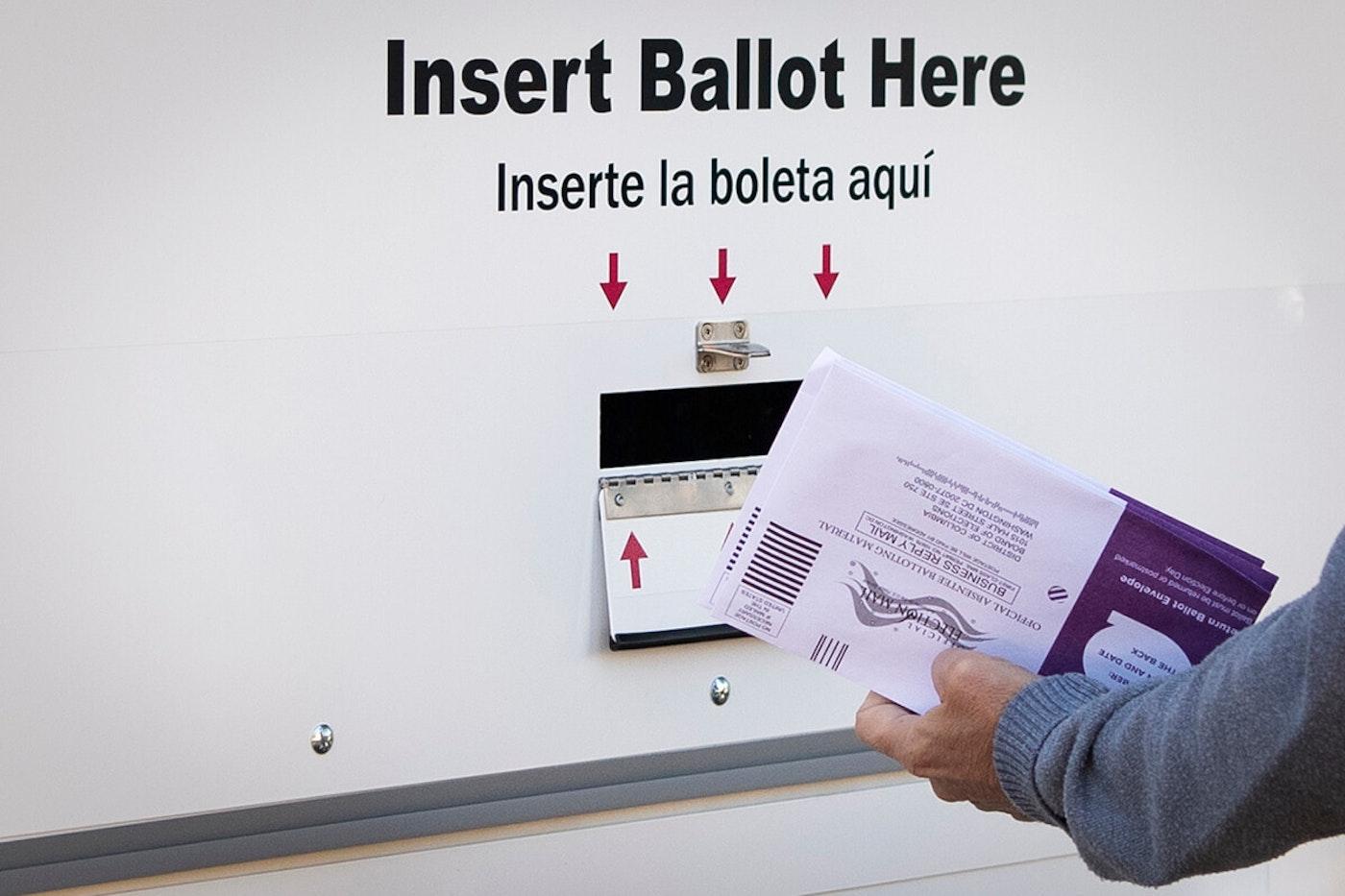 hand holding early ballots up to ballot drop box slot