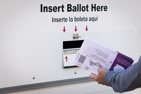 hand holding early ballots up to ballot drop box slot