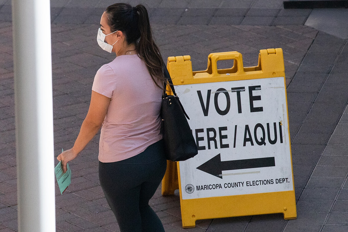 woman wearing masks walks past vote here sign