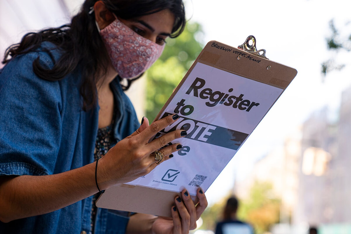 "woman holds clipboard that says ""register to vote here"""