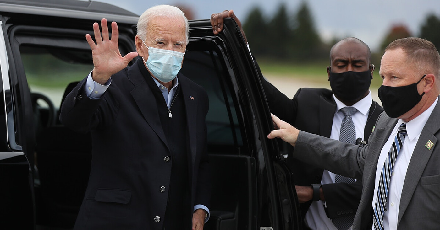 GRAND RAPIDS, MICHIGAN - OCTOBER 02: Wearing a mask to reduce the risk posed by the coronavirus, Democratic presidential nominee Joe Biden waves while preparing to board his plane  after campaigning. Biden said he tested negative twice Friday for the coronavirus after it was reported that U.S. President Donald Trump and first lady Melania Trump tested positive for COVID-19. (Photo by Chip Somodevilla/Getty Images)