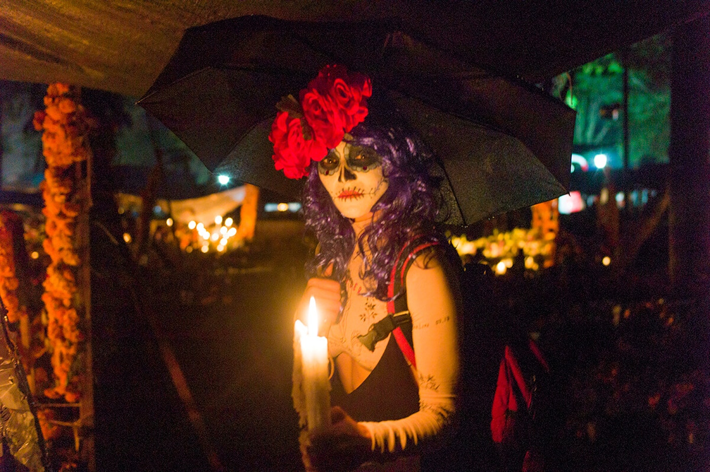 a woman in Day of the Dead makeup holds a candle while posing in the dark