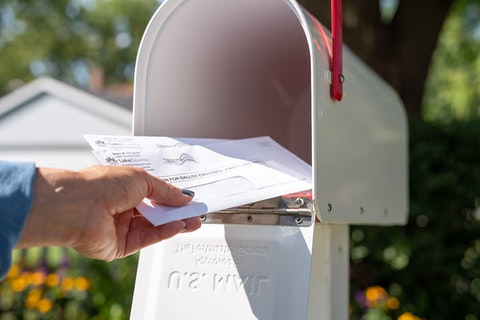 woman's hand placing ballot in home mailbox with flag up