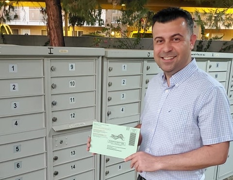 Bilal Alobaidi holding his ballot in front of mailboxes