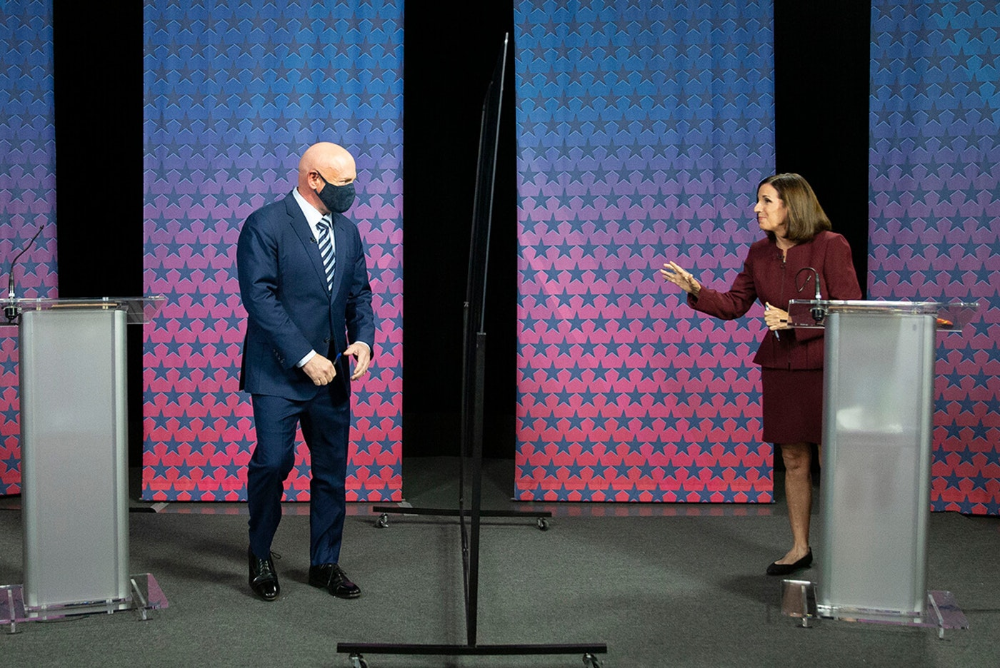 Mark Kelly and Martha McSally facing each other on debate stage