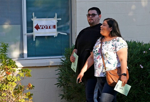 Voters arrive at a polling station with their ballots ready to be turned in on primary election day Tuesday, Aug. 28, 2018, in Phoenix. (AP Photo/Ross D. Franklin)