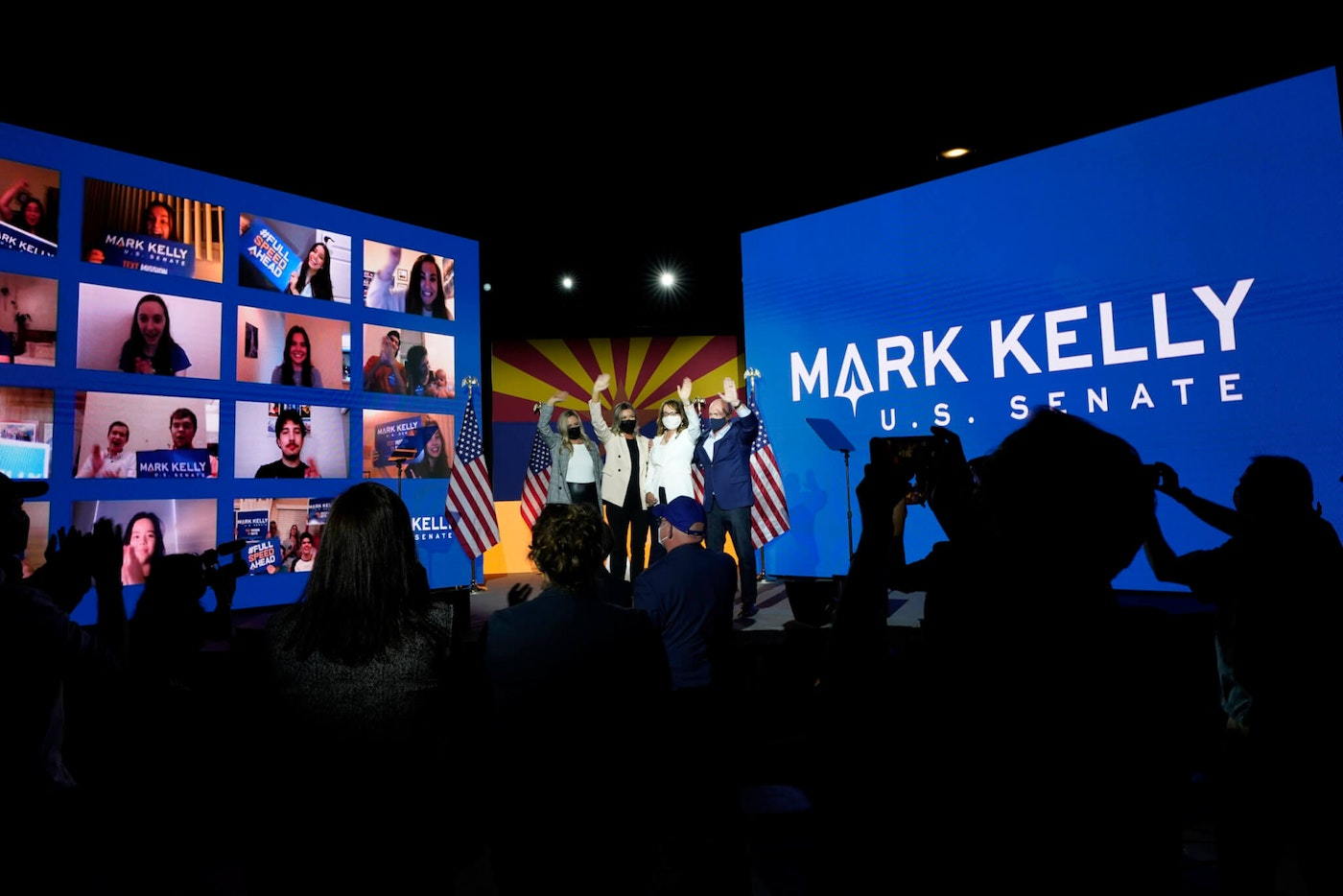 Mark Kelly, right, Arizona Democratic candidate for U.S. Senate, waves to supporters along with his wife Gabrielle Giffords, second from right, and daughters, Claire Kelly, left, and Claudia Kelly, second from left, during an election night event Tuesday, Nov. 3, 2020 in Tucson, Ariz. (AP Photo/Ross D. Franklin)