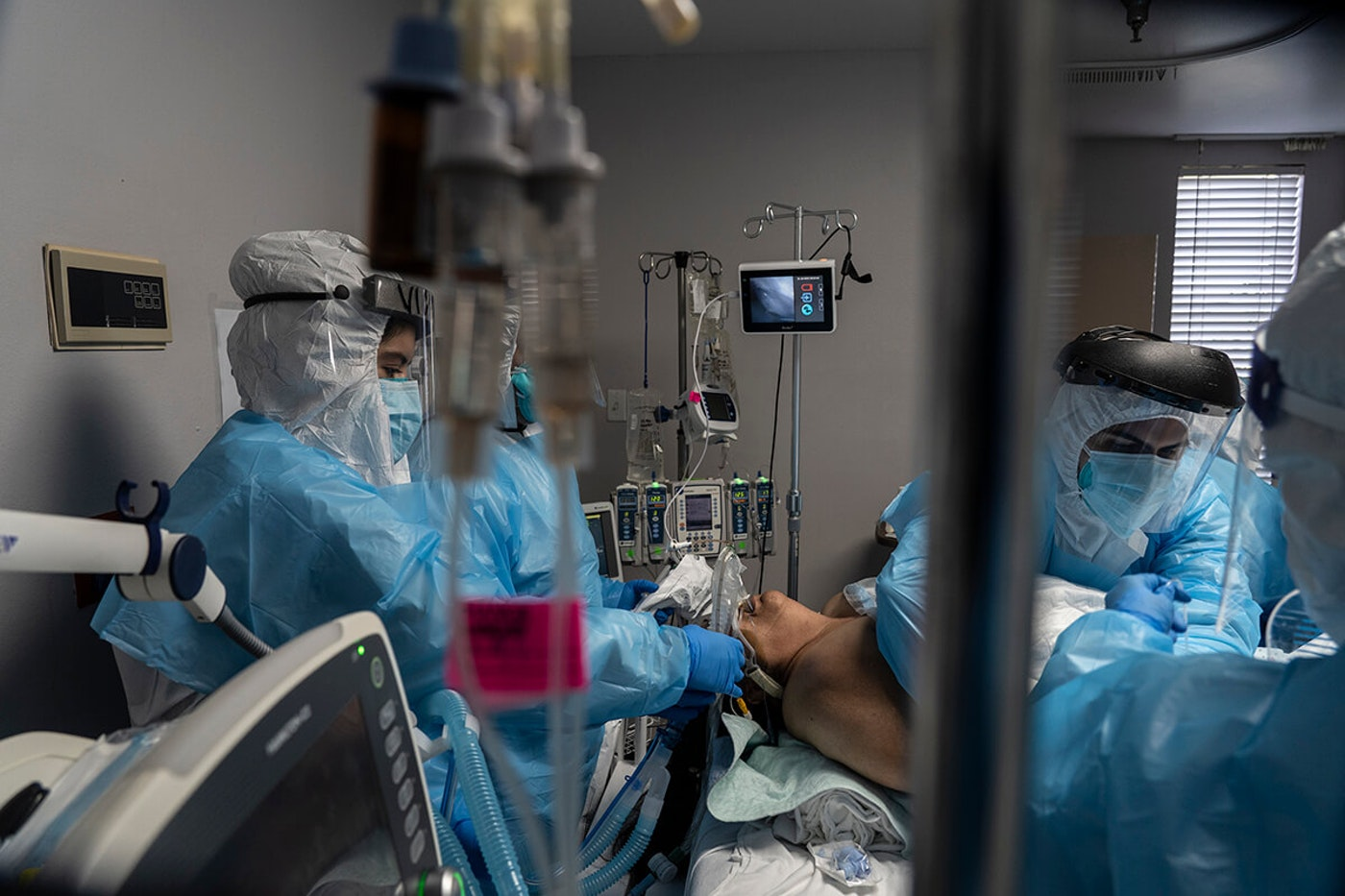 medical workers in full COVID gear surround intubated patient
