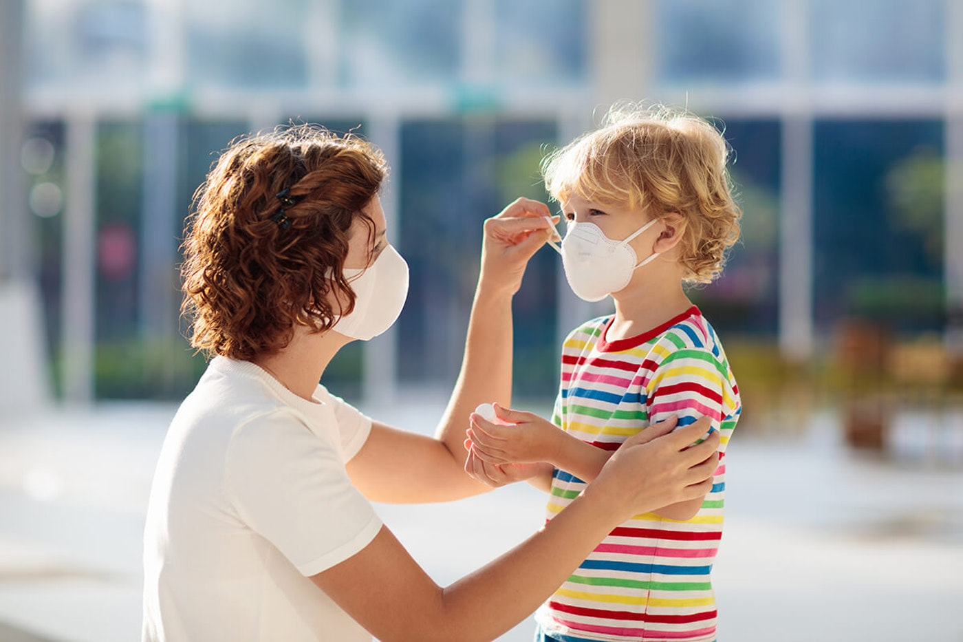 woman wearing masks kneeling and adjusting mask on young boy's face