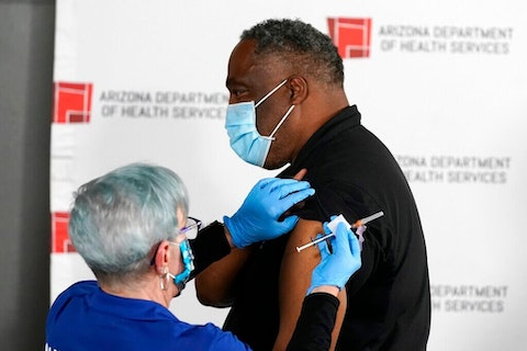 Dr. Edmund Baker, right, receives the Pfizer-BioNTech vaccine for COVID-19 at the Arizona Department of Health Services State Laboratory from nurse Machrina Leach, Wednesday, Dec. 16, 2020, in Phoenix.