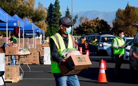 "Food is loaded as drivers in their vehicles wait in line on arrival at a ""Let's Feed LA County"" food distribution hosted by the Los Angeles Food Bank on December 4, 2020 in Hacienda Heights, California. - While coronavirus cases continue to surge nationwide and shutdowns return, the US economic recovery stalls with just 245,000 jobs in the final report of 2020 as the unemployment rate fell to 6.7 percent, according to Bureau of Labour Statistics. (Photo by FREDERIC J. BROWN/AFP via Getty Images)"