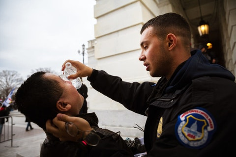 A Trump supporter is tended to by a police officer while suffering the effects of chemical agents used to disperse crows after protesters stormed the grounds the Capitol Building on January 6, 2021 in Washington, DC. (Photo by Jon Cherry/Getty Images)