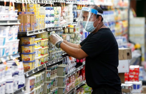 Amid concerns of the spread of COVID-19, a worker restocks products at a grocery store in Dallas, Wednesday, April 29, 2020.