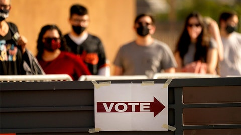 Voters stand in line outside a polling station, on Election Day, Tuesday, Nov. 3, 2020, in Mesa, Ariz. (AP Photo/Matt York)