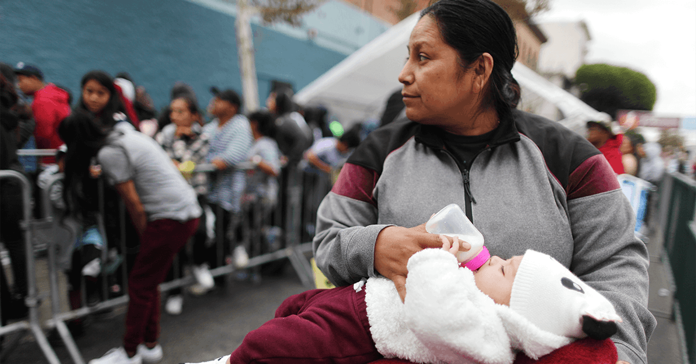 A woman feeds a baby as people wait in line to receive new school supplies, including new athletic shoes donated by Foot Locker, at Fred Jordan Missions on Skid Row, on September 28, 2019 in Los Angeles, California. Fred Jordan Missions, which feeds over 100 people experiencing homelessness daily, hosts the annual event with Foot Locker. They donated new sneakers and other school supplies to more than 3,000 underprivileged and homeless children this year.