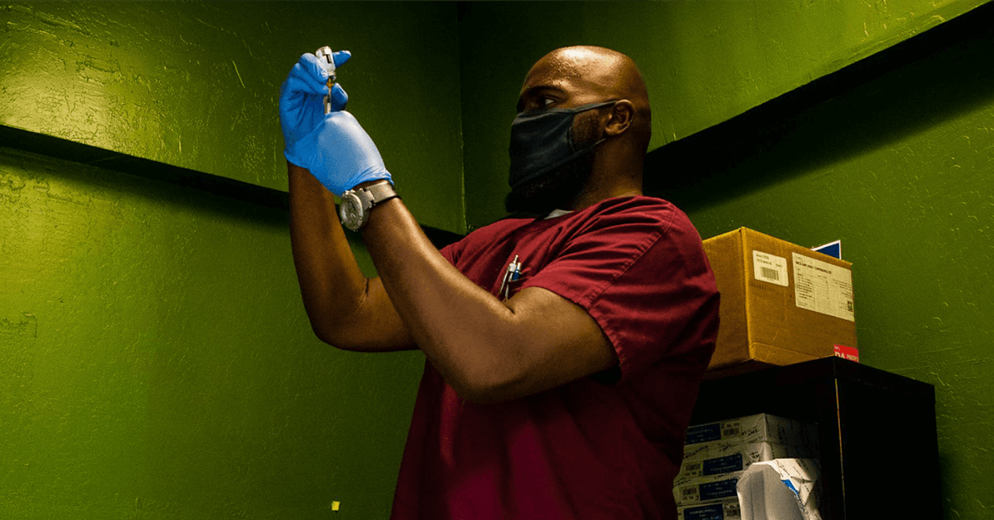 Christopher Sims, a Commerce Medical Group nurse, prepares a syringe as Patrick Brown waits for his second vaccination shot at Mint Dispensary in Mesa, Arizona, on June 2, 2021. Brown came to the dispensary not because of the offer of free marijuana products but because it's close to his apartment.