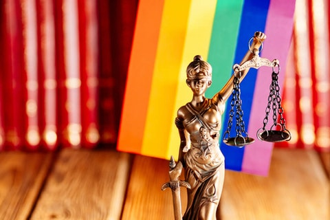 state of women holding legal scales in front go LGBTQ pride flag and books
