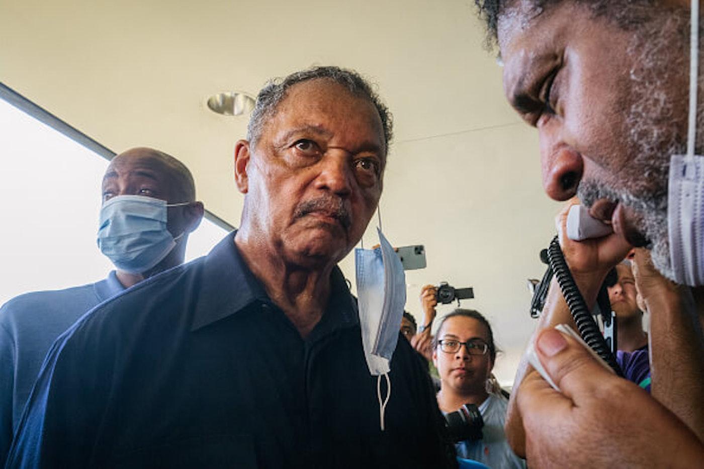 Rev. Jesse Jackson (C), listens during a sit-in demonstration outside the office of Sen. Kyrsten Sinema (D-AZ) on July 26, 2021 in Phoenix, Arizona.