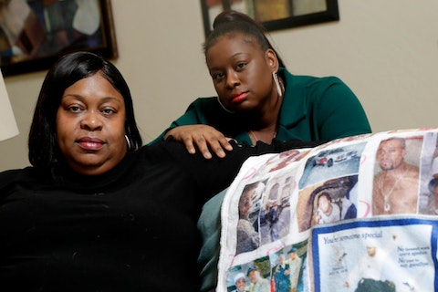 two Black women holding quilt with photos of relative who was killed by police