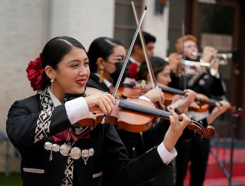 a line of people dressed in mariachi garb playing the violin