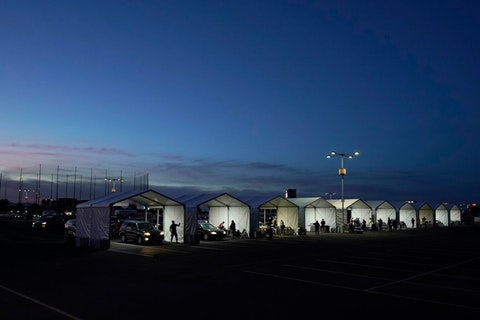 wide shot of COVID-19 vaccination tents set up outside of State Farm Stadium with dark blue sky