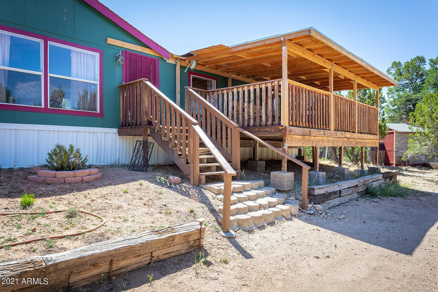 front of a home with teal and magenta paint and a large wooden outdoor covered deck