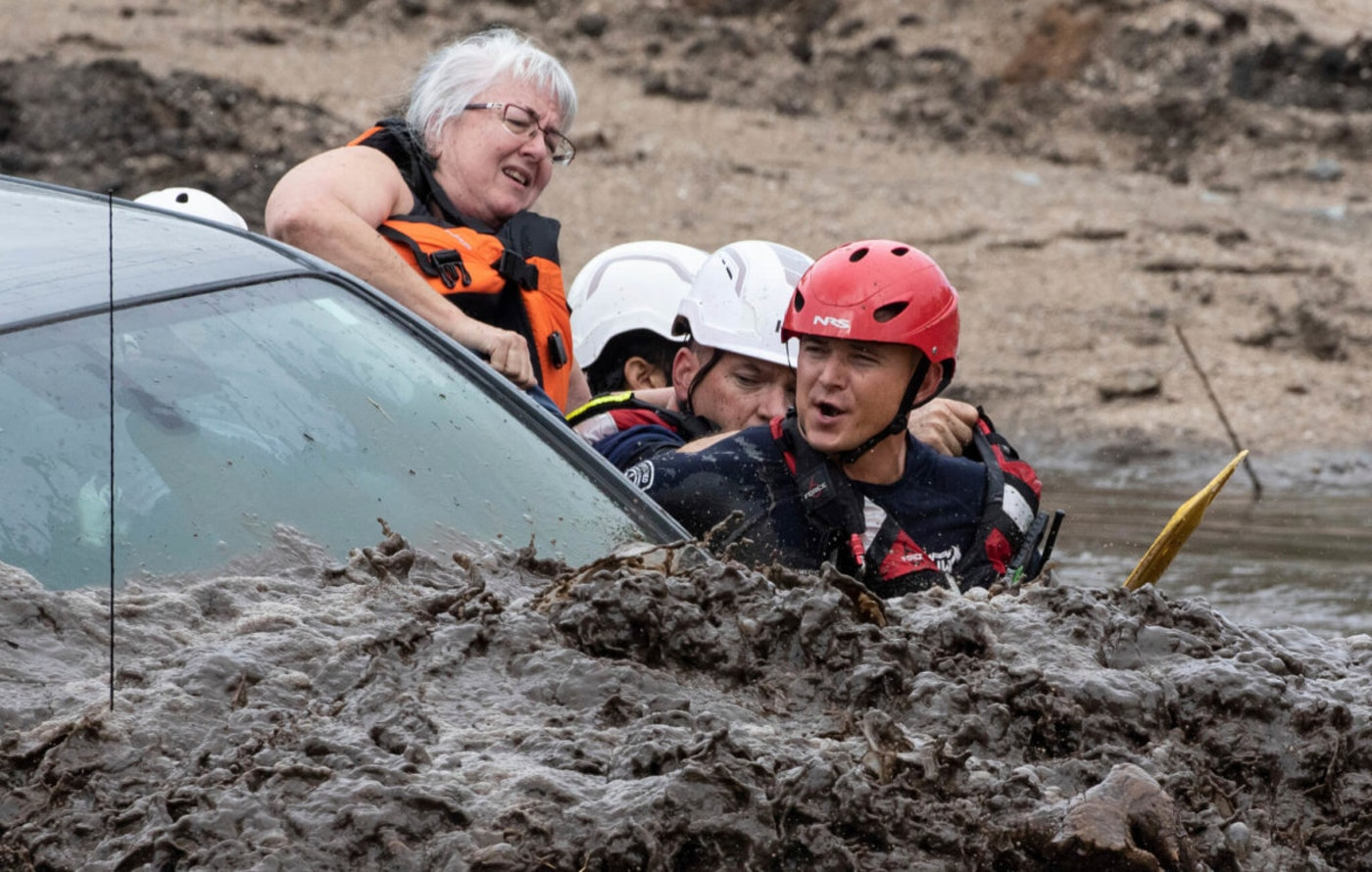 a woman halfway out of a car as three rescuers pull her out amid flood waters