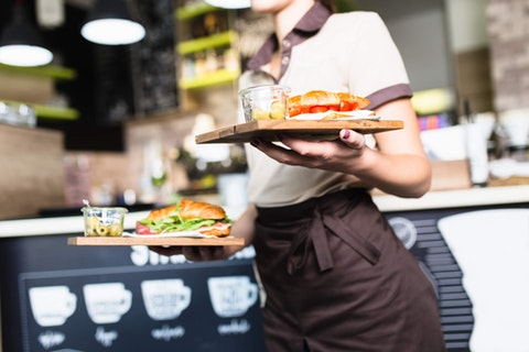 waitress bringing out two trays with food on them
