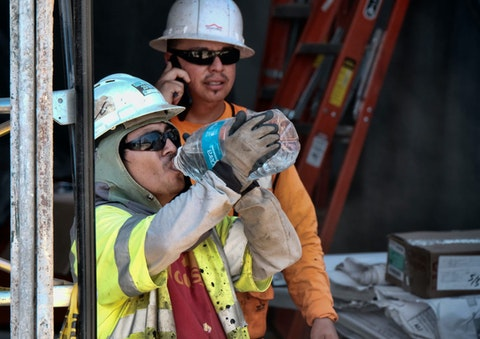 two construction workers, one in front drinking from large water bottle