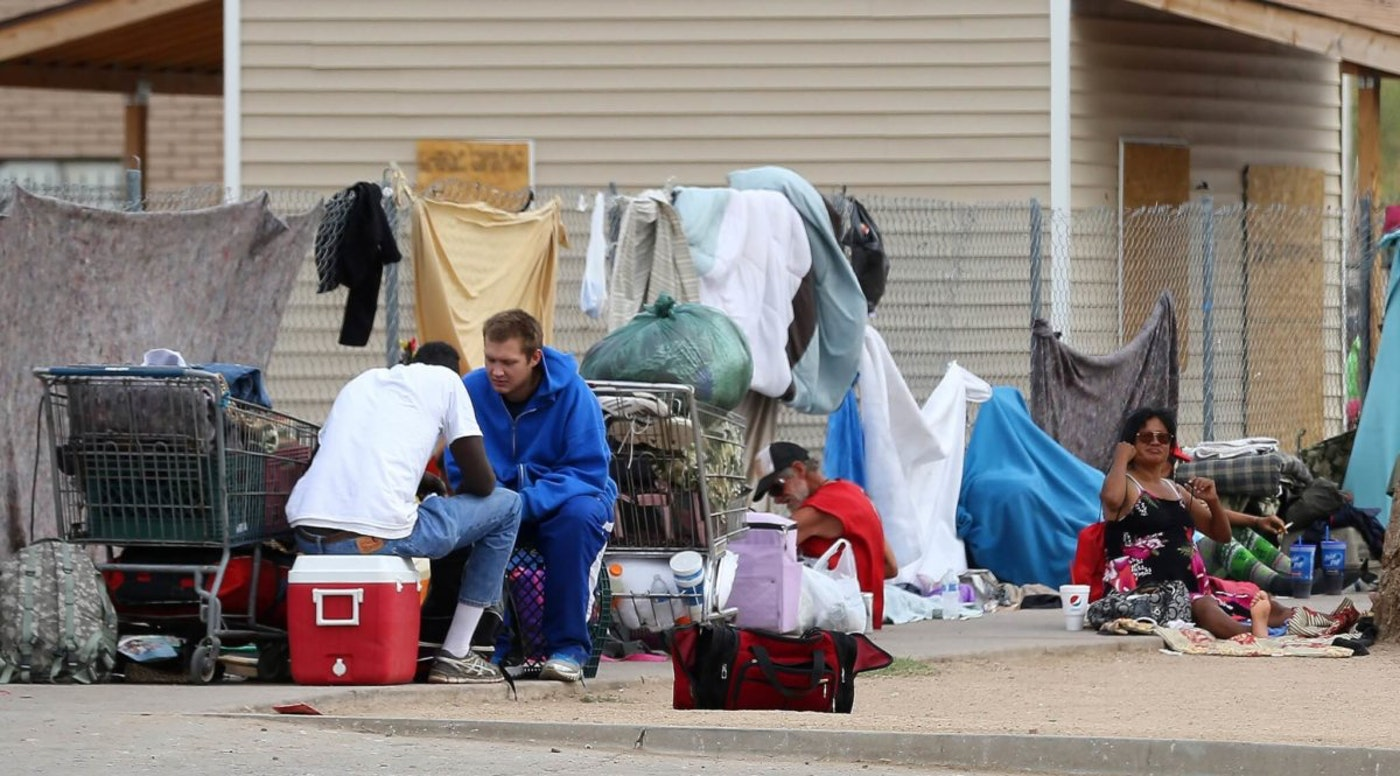 a homeless camp on a Phoenix street corner showing people sitting with their belongings on a sidewalk