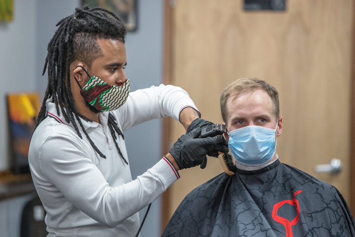 Kevin Rivera, barber at Midwood Barbers in Charlotte, cuts hair in late May while wearing a mask. Masks are required in personal care businesses like salons, but NC is considering a mandatory mask rule in all public spaces. (Photo for Cardinal & Pine by Grant Baldwin)